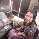 Girl cooking tortillas on wood stove in Guatemala.